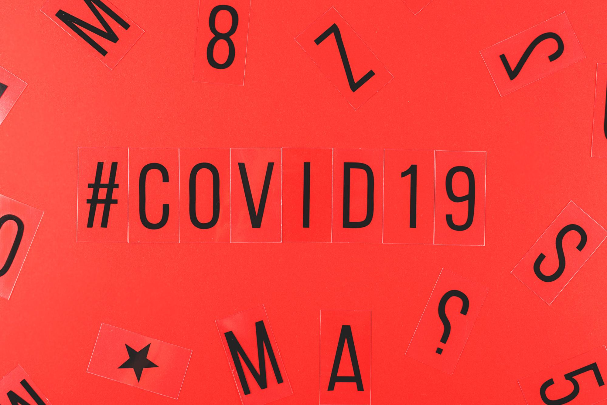 Word covid-19 and hashtag on red background